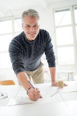 Architekt zeichnet in seinem Buero