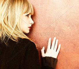 Blonde Frau lehnt sich gegen eine Wand