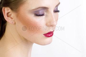 Studioaufnahme einer jungen Frau  Detailaufnahme vom Gesicht mit Schminke und kuenstlichen Augenlidern  young woman  with artificial eyelid