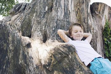 Boy leaning against big tree trunk