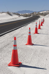 Traffic cones along a paved road through White Sands National Monument  New Mexico  USA