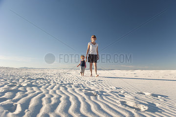 Mother and son walking on dune  White Sands National Monument  New Mexico  USA