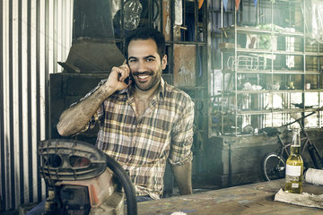 Man taking break for phone call and beer