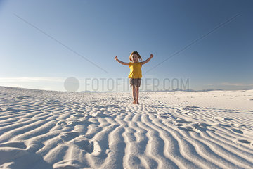 Girl walking on dune  White Sands National Monument  New Mexico  USA