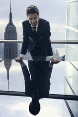 Businessman leaning against table  reflection in glass top