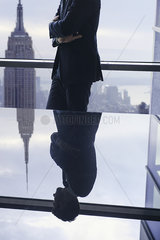 Businessman with arms folded looking away  reflection in glass top table