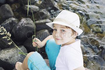 Boy sitting by stream