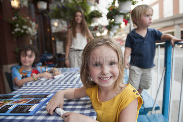 Little girl sitting at outdoor cafe  portrait