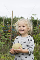 Little girl with cantaloupe in garden