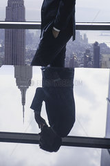Businessman using cell phone  reflection in glass table top