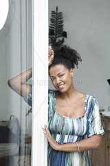 Woman leaning in doorway  smiling  portrait