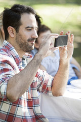 Man taking picture with smartphone at gathering with friends