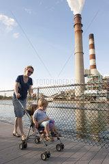Mother pushing children in stroller near power plant