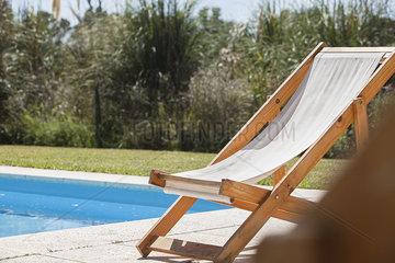 Deckchair beside swimming pool