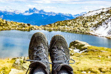Hiking boots in the mountains in front of a lake