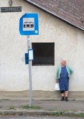 Dorfbewohnerin an einer Bushaltestelle