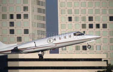Bombardier Learjet taking-off with office buildings behind