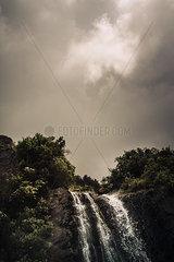Dunkle Wolken ueber einem Wasserfall