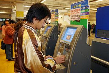 Hong Kong  Mann wettet an einem elektronischen Wett-Terminal auf der Galopprennbahn Sha Tin