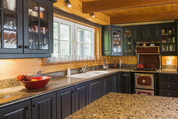 Kitchen with black wooden cabinets  antique cooking stove and granite countertops inside a milled cottage style flat log profile home; Quebec  Canada
