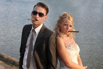 Berlin  Deutschland  ein Brautpaar posiert mit Zigarre als Mafiapaerchen
