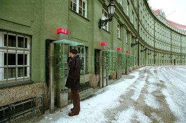 Mann telefoniert mit oeffentlichem Telefon im Winter