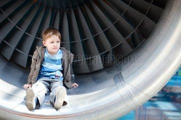 Small boy sitting inside aircraft engine