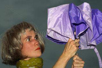 Berlin  Frau oeffnet einen klemmenden Regenschirm vor dunklem Himmel