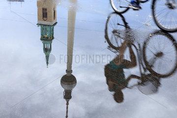 Berlin  Deutschland  Spiegelung von einem Radfahrer und Fernsehturm in einer Pfuetze am Alexanderplatz in Berlin-Mitte