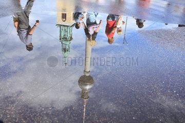 Berlin  Deutschland  Spiegelung von Passanten und Fernsehturm in einer Pfuetze am Alexanderplatz in Berlin-Mitte