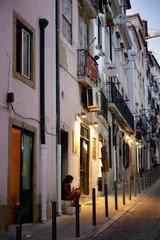 Lissabon  Portugal  Frau sitzt auf Stufen in Alfama in Lissabon