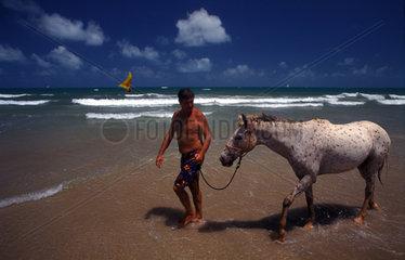 Mann mit Pferd an der Kueste in Brasilien