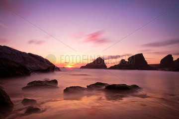 Bedruthan Steps at sunset with violet skies  Cornwall  England