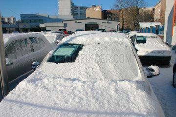 Schneebedeckte Autos vor einem Autohaendler