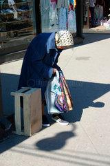 Riga. Eine Aeltere Frau beim Verkauf von Plastik Einkaufstueten.