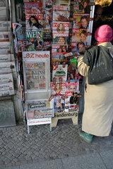 Frau vor ein Zeitungskiosk