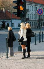 Frauen an eine Fussgaengerampel in Vilnius.