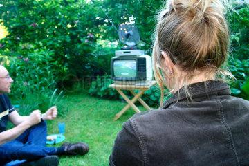 Germany. Berlin - Menschen verfolgen eine Fussball WM Spiel in ein klein Garten