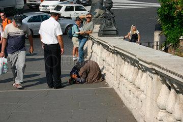 ein Vigile verscheucht eine Bettlerin in Rom