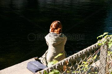Berlin. Junge Frau beim telefonieren am Spreeufer