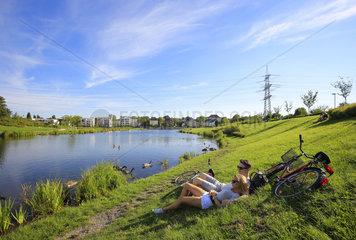 Essen  Ruhrgebiet  Deutschland  staedtebauliches Projekt Niederfeldsee  jugendliches Paar liegt in auf der Wiese
