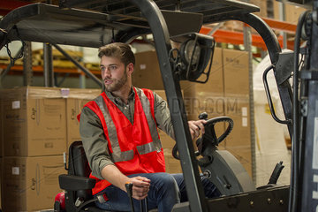 Worker operating forklift truck