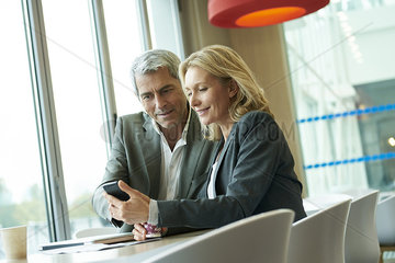 Businesspeople using smart phone in cafeteria