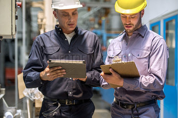Factory workers with digital tablet and clipboard in factory