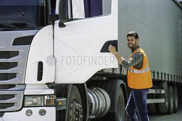 Worker opening door of lorry