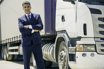 Businessman standing in front of lorry