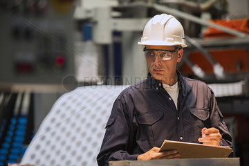 Factory worker with clipboard in factory