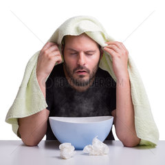 A man is suffering from the flu and inhales steam to get healthy isolated on white background.
