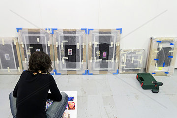 Artist looking at wrapped images at art fair
