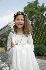 Riedlingen  Deutschland  Maedchen im Kommunionskleid mit Kommunionkerze
